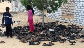 Egyptian children stand near a pile of footwear belonging to the victims of the attack at the Al-Rawdah Mosque near the town of Bir al-Abd in North Sinai, November 25, 2017.