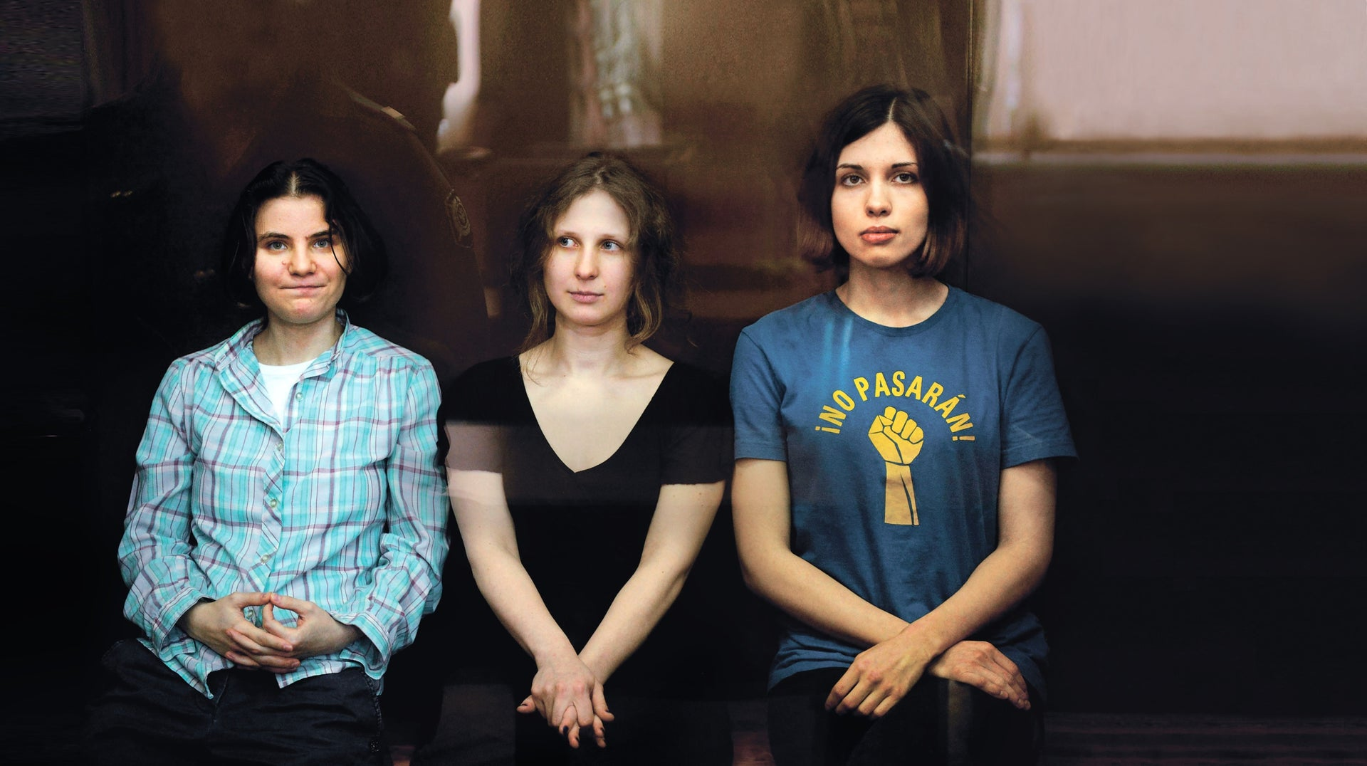 Members of Pussy Riot, Nadezhda Tolokonnikova (right), Maria Alyokhina (center) and Yekaterina Samutsevich (left) sit in a glass-walled cage during a court hearing in Moscow, Agust 17, 2012.
