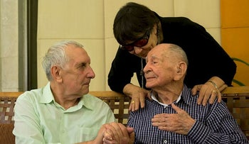 In this Thursday, Nov. 16, 2017 photo, Israeli Holocaust survivor Eliahu Pietruszka, right, speaks with Alexandre Pietruszka as they meet for the first time in the central Israeli city of Kfar Saba.