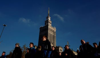 People walk near the Palace of Culture and Science in the morning in Warsaw, Poland November 23, 2017.