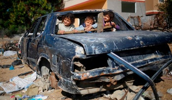 Palestinian children play in an old car next their house in Beit Hanun in the northern Gaza Strip, November 24, 2017.