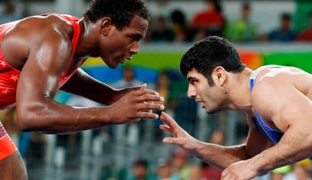 J'den Michael Tbory Cox (U.S.) wrestles with Alireza Mohammad Karimimachiani (Iran) during the wrestling event of the Rio 2016 Olympic Games at the Carioca Arena 2 in Rio de Janeiro.