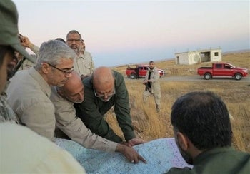 FILE PHOTO: Iran's army chief of staff Maj. Gen. Mohammad Bagheri, left, looking at a map with senior officers from the Iranian military as they visit a front line in the northern province of Aleppo, Syria.