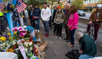 A group pauses at a makeshift memorial that honors victims of a truck-ramming attack on Halloween in New York, November 4, 2017.