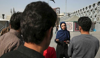In this Monday, Nov. 6, 2017 photo, Samira Ghavipanjeh, a member of Reviving Values aid group, tries to convince passers by to get tested for HIV, in Tehran, Iran
