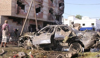 A man stands by a damaged car at the site of a car bomb attack outside the Finance Ministry offices in the southern port city of Aden, Yemen November 29, 2017