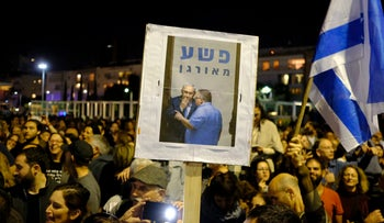 Demonstrators in Tel Aviv raise a sign of coalition whip David Bitan and Prime Minister Benjamin Netanyahu with the word 'crime' in Hebrew on Saturday, December 2.