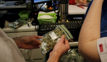 An employee holds a package of medical marijuana as he works at a dispensary belonging to Tikun Olam, Israel's largest medical marijuana supplier, in Tel Aviv March 27, 2016.