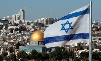 The Israeli flag flutters in front of the Dome of the Rock mosque and the city of Jerusalem, December 1, 2017.