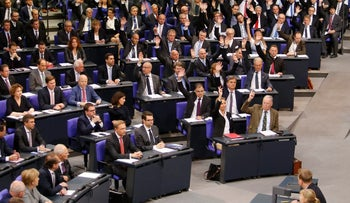 German Chancellor Angela Merkel, bottom left, watches the far right Alternative for Germany (AfD) faction demanding a procedural change during the first post-election session meeting of the German parliament. Berlin, Oct. 24, 2017