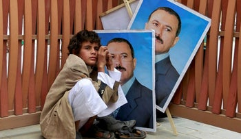 A young boy sits with posters of Yemen's President Ali Abdullah Saleh during Friday prayers ahead of a rally to show support for Saleh in Sanaa, Yemen August 12, 2011