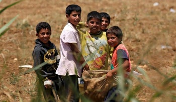 Syrian refugee boys hold a bag at a camp for Syrian refugees near the town of Qab Elias, in Lebanon's Bekaa Valley, August 8, 2017. Picture taken August 8, 2017