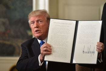 U.S. President Donald Trump holds up a signed memorandum after he delivered a statement on Jerusalem from the Diplomatic Reception Room of the White House in Washington, DC on December 6, 2017.