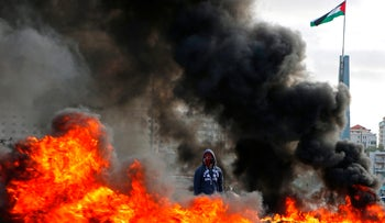 A Palestinian protester stands between burning tyres during clashes with Israeli troops near the West Bank city of Ramallah on December 7, 2017.