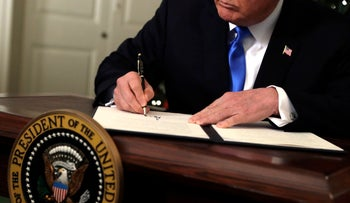 U.S. President Donald Trump signs a memorandum Wednesday, November 6 at the White House after announcing his official recognition of Jerusalem as Israel's capital.