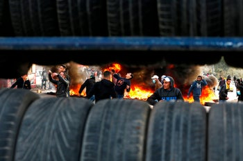 Palestinian protesters clash with Israeli troops following a protest against US President Donald Trump's decision to recognize Jerusalem as the capital of Israel, near the Jewish settlement of Beit El, near the West Bank city of Ramallah, on December 7, 2017.  / AFP PHOTO / ABBAS MOMANI