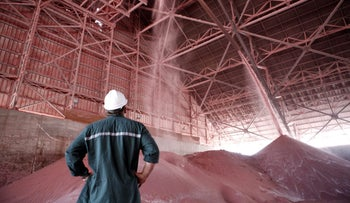 An employee watches as red potash is deposited onto storage mounds inside a warehouse at ICL Fertilizer's Dead Sea Works, part of Israel Chemicals Group, on the Dead Sea, Israel, on Monday, May 6, 2013. Israel Chemicals Ltd. advanced the most in more than a week on bets declines last month after Potash Corp. of Saskatchewan Inc. scrapped a proposed takeover bid were overdone. Photographer: Ariel Jerozolimski/Bloomberg