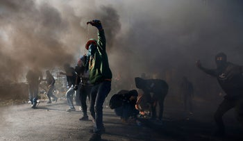 Palestinian protesters clash with Israeli troops near an Israeli checkpoint in the West Bank city of Ramallah on December 8, 2017.