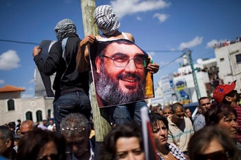 Protesters in the Israel-Arab town of Sakhnin during Land Day demonstrations in 2010. One of the protesters holds an image of Hezbollah leader Hassan Nasrallah.