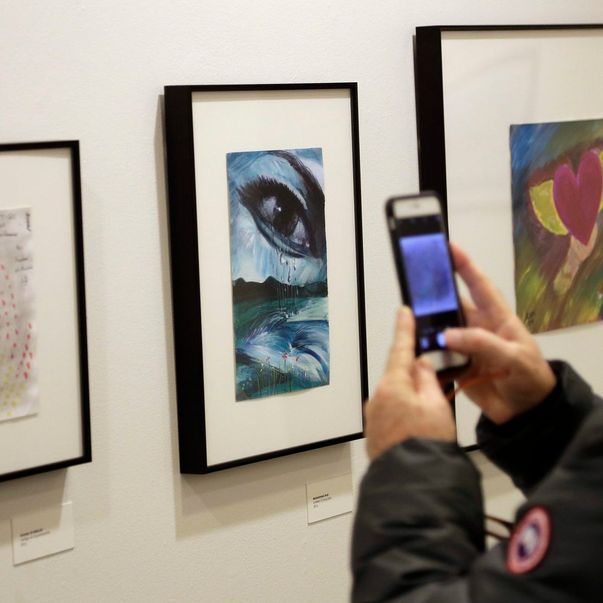 A man takes a picture of artwork made by detainees of the Guantanamo Bay Detention Camp at an exhibit at at the John Jay College of Criminal Justice in New York.