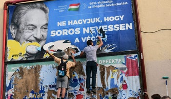 Activists from the Egyutt (Together) party tear down an ad by the Hungarian government against George Soros, Budapest, July 12, 2017.