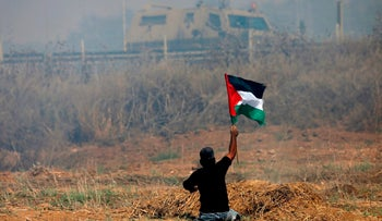 (FILES) This file photo taken on May 19, 2017 shows handicapped Palestinian demonstrator Ibrahim Abu Thurayeh waving a Palestinian flag during clashes with Israeli soldiers following a protest against the blockade on Gaza, near the border fence east of Gaza City.