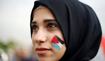 A Palestinian woman painted on her face a Palestinian flag during a march in the streets of Beirut, Lebanon, Friday, Dec. 8, 2017, against U S. President Donald Trump's decisions to recognize Jerusalem at the capital of Israel in Beirut.