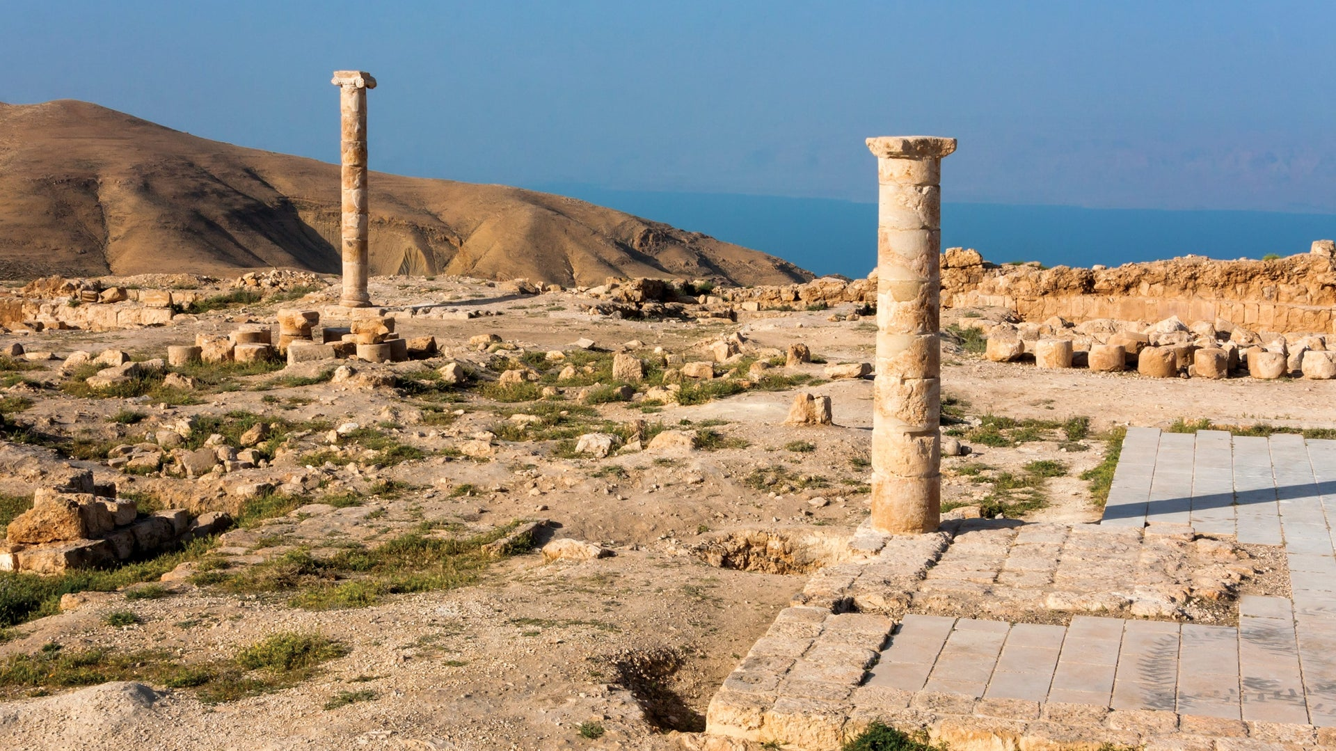 Two re-erected columns—one Doric (right) and one Ionic—stand tall atop Machaerus with the Dead Sea in the background. The Doric column is shorter, stumpier and with a plain capital. The Ionic column is taller, slenderer and with a fancy scroll capi-tal.