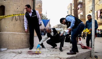 Egyptian security members and forensic police inspect the site of a gun attack outside a church south of the capital Cairo, Egypt, December 29, 2017.