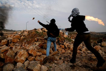 Palestinian protesters molotov cocktails towards Israeli security forces during clashes in the West Bank city of Ramallah on December 29, 2017.