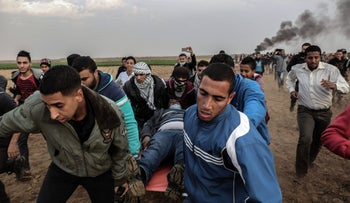 FILE PHOTO: Palestinian protesters carry a wounded man during clashes with Israeli forces near the Israel-Gaza border, December 29, 2017.