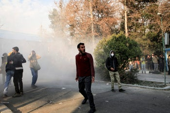 University students attending a protest inside Tehran University while a smoke grenade is thrown by anti-riot Iranian police, December 30, 2017.