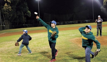 Ezra Schwartz's brothers tossing the first pitch at the All-Star game at Baptist Village on Tuesday.