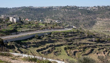 The homes of Al-Walaja looking down on the agricultural terraces and a barbed-wire Israeli fence.