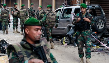 Lebanese army soldiers stand guard at the site of Thursday's twin suicide bombings in Burj al-Barajneh, southern Beirut, Lebanon, Friday, Nov. 13, 2015.