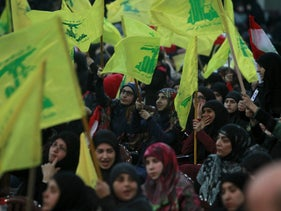 Supporters of Lebanon's Hezbollah leader Sayyed Hassan Nasrallah wave Hezbollah flags as they listen to him through a giant screen during a rally commemorating the annual Hezbollah Martyrs' Leader Day in Beirut's southern suburbs, Lebanon February 16, 2016.