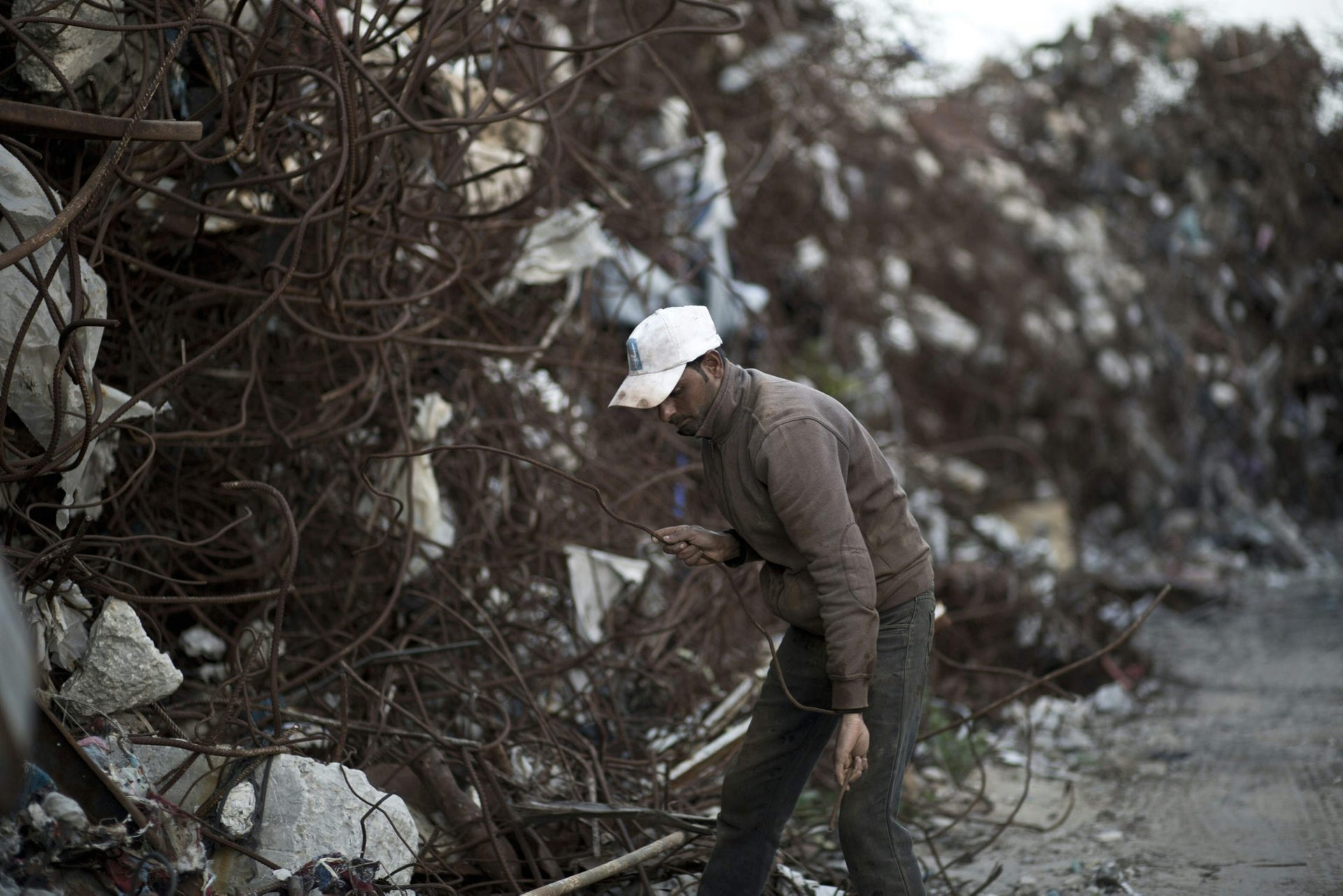 A Palestinian worker selects metal pieces in East Gaza City, on February 20, 2016.