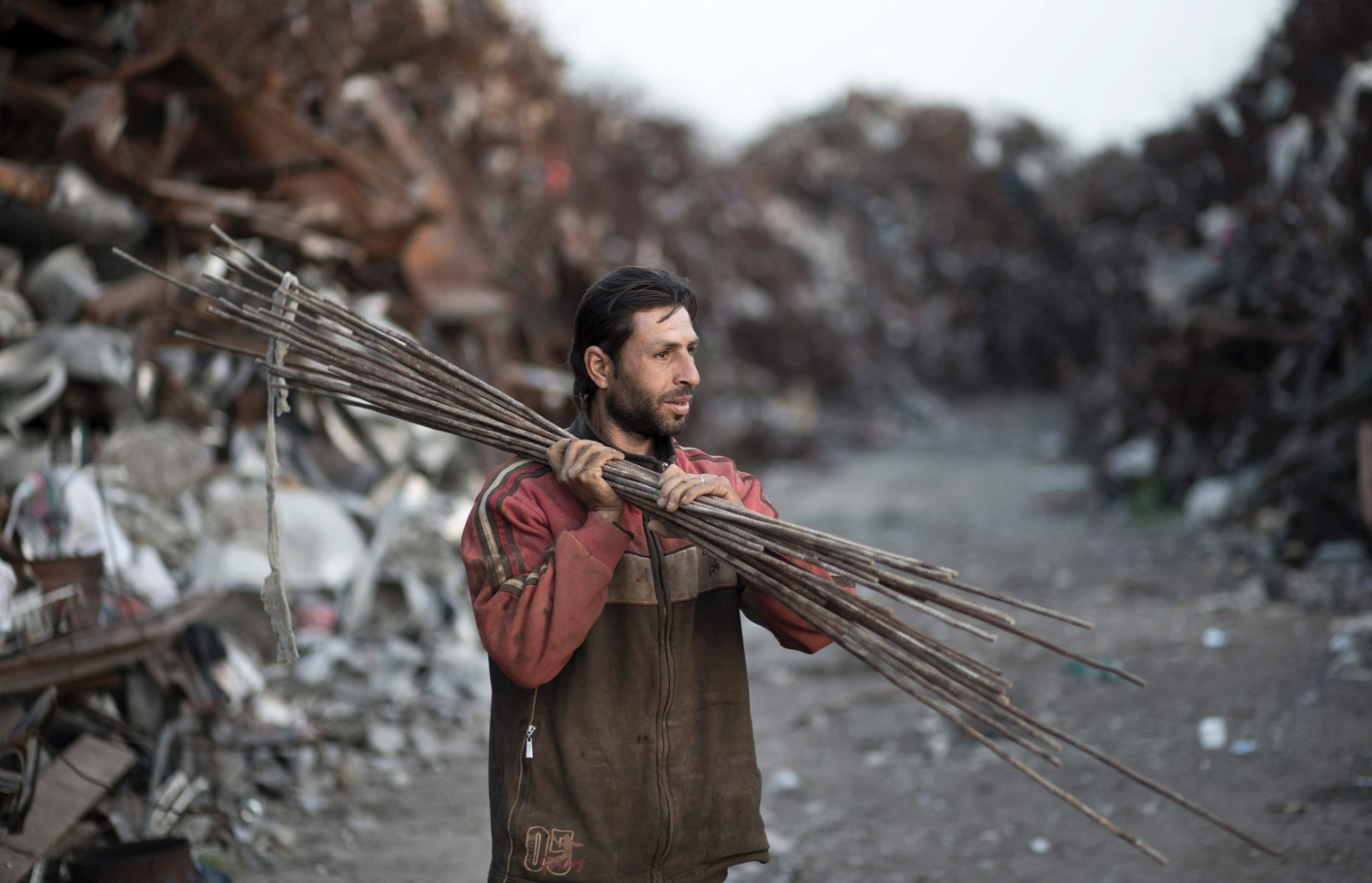 A Palestinian worker carries metal sticks in East Gaza City, on February 20, 2016.