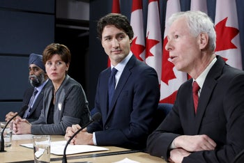 Canada's Prime Minister Justin Trudeau (2nd R) listens to Foreign Minister Stephane Dion (R) speak during a news conference in Ottawa, Canada, February 8, 2016.