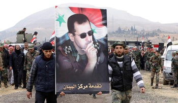 Syrians wave the national flag and portraits of President Bashar Assad north of Damascus on February 22, 2016.