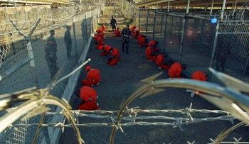 Detainees in orange jumpsuits sit in a holding area under the watchful eyes of military police during in-processing to Guantanamo Bay in 2002.