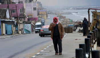 A Palestinian man smokes while walking on the main beach road after rainstorm near the Shati refugee camp in Gaza City, January 26, 2016.
