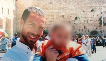 Eliav Gelman pictured at the Western Wall with one of his children