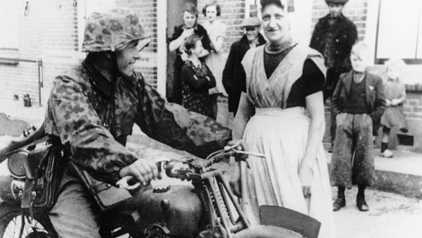A German motorcycle rider talking with a Dutch peasant woman, at an unknown location in Holland, May 24, 1940. Both are smiling.