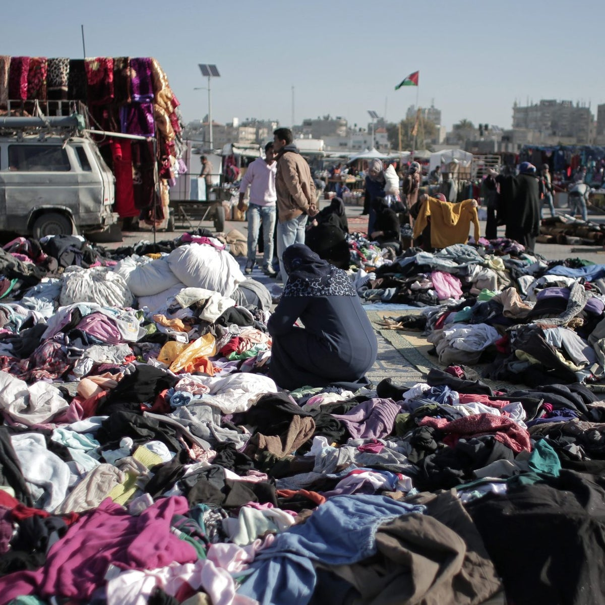 A Palestinian woman sifts through used clothes at the weekly flea market in Nusseirat refugee camp, central Gaza Strip, Feb. 15, 2016.