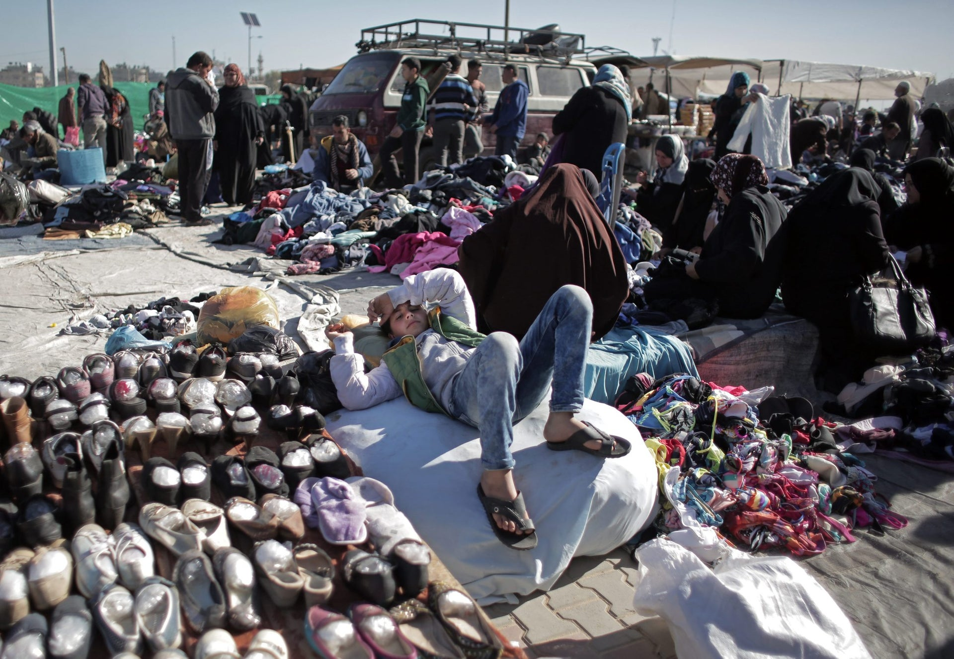A Palestinian boy lays next to displayed used shoes for sale at the weekly flea market in Nuseirat refugee camp, central Gaza Strip, February 15,2016.
