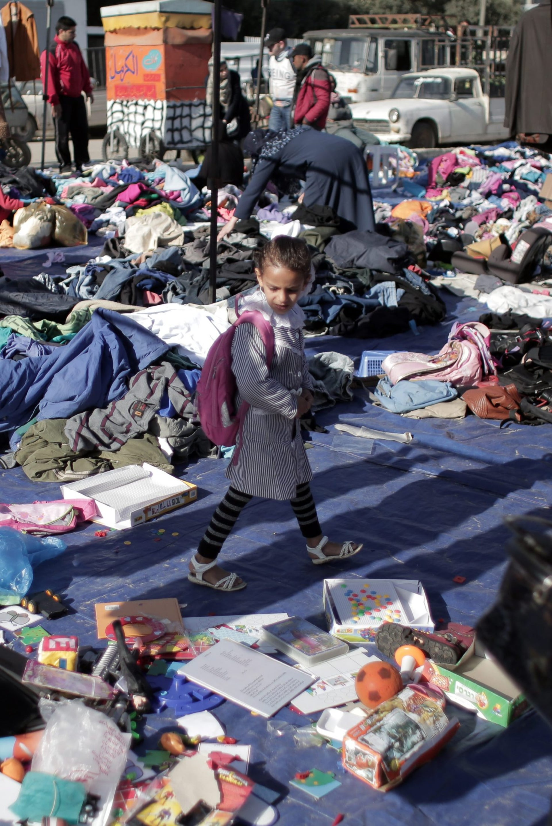 A Palestinian schoolgirl looks at used toys and clothing at the weekly flea market in Nusseirat refugee camp, central Gaza Strip, Feb. 15, 2016.
