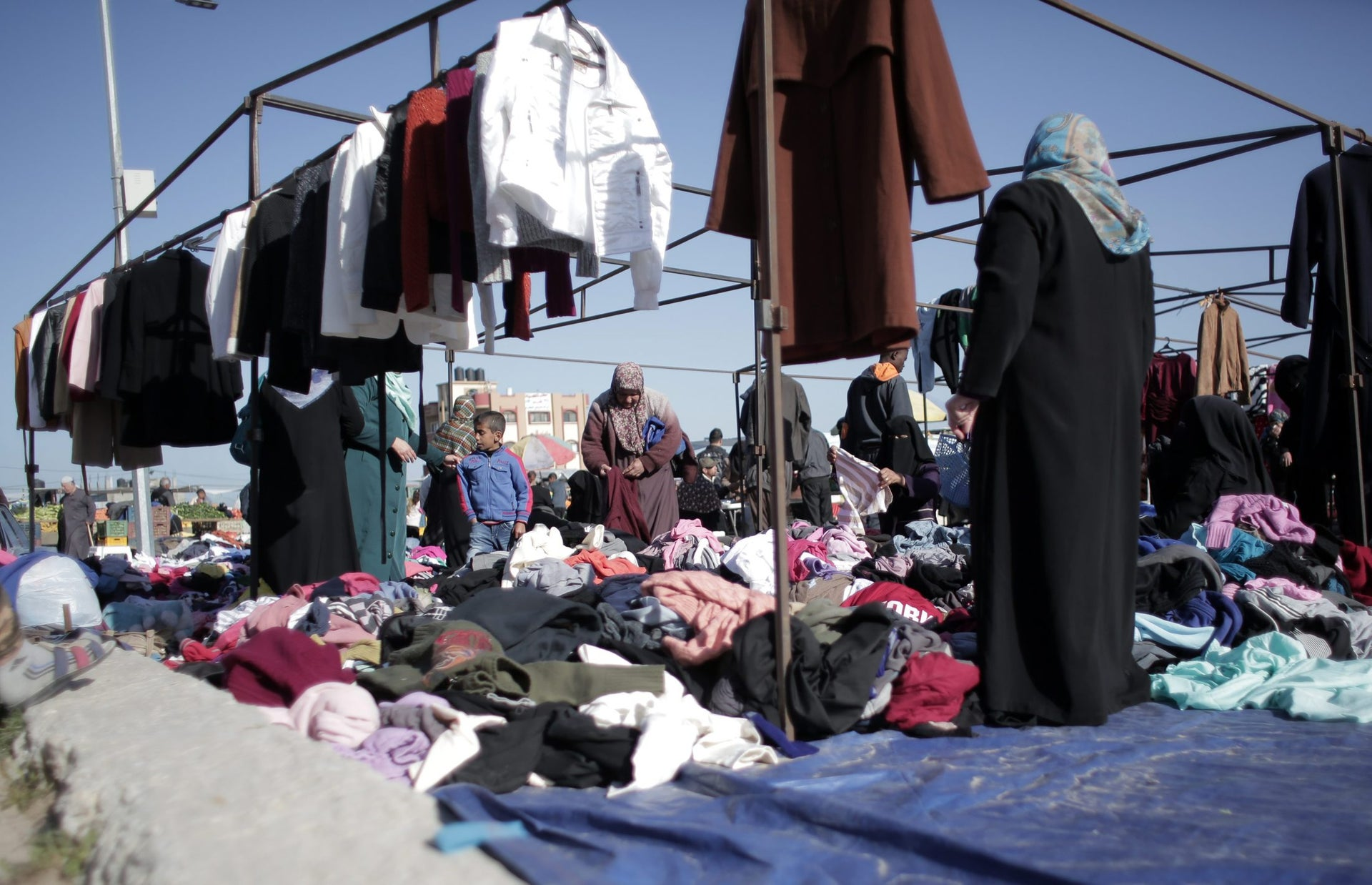 Palestinian women sift through used clothing at the weekly flea market in Nusseirat refugee camp, central Gaza Strip,  Feb. 15, 2016.