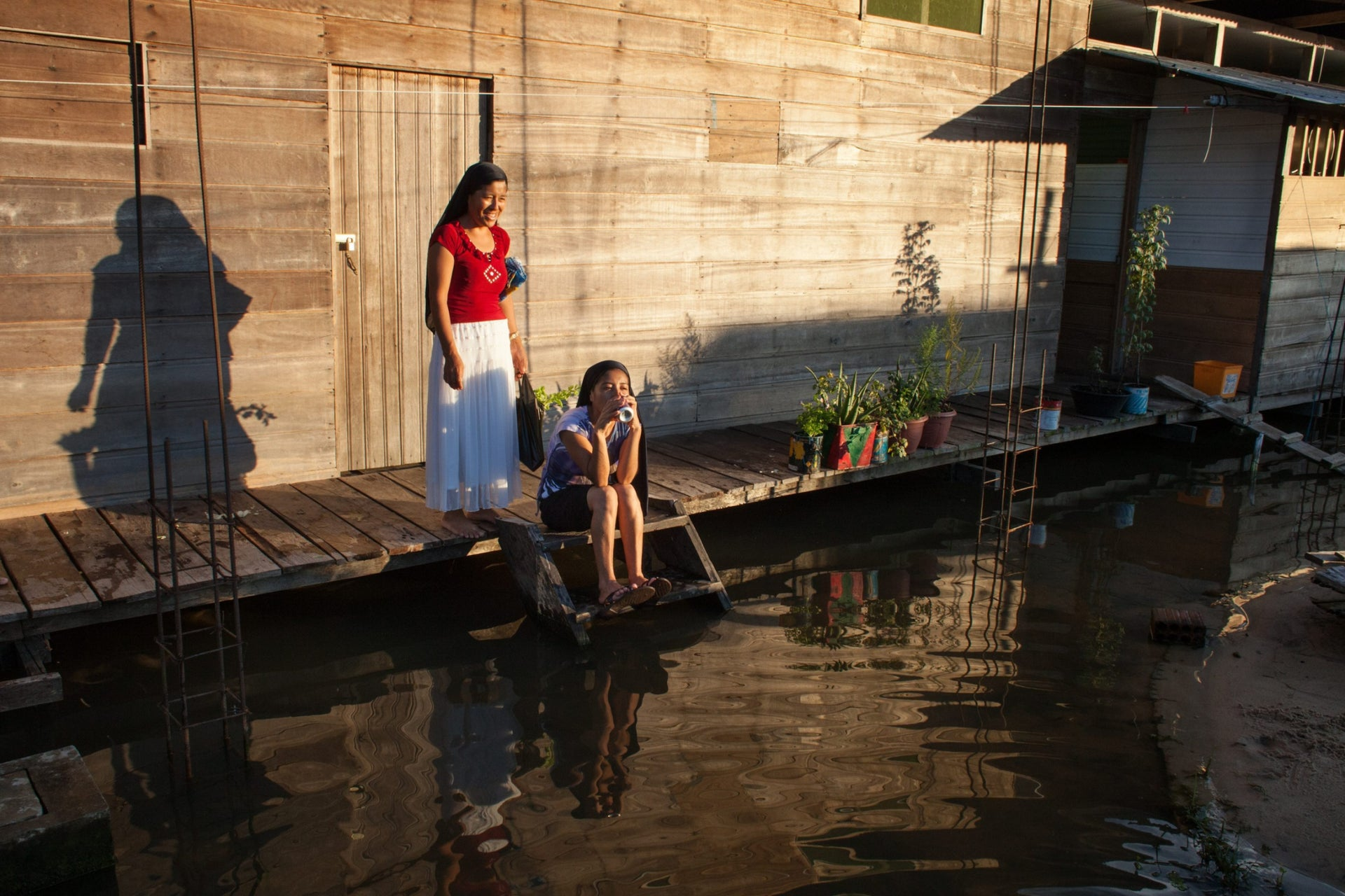 Young women from the New Israelite community in Islandia, Peru, sit next to a flooded street.