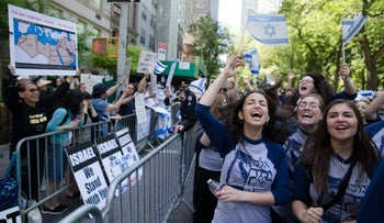 Marchers cheer as they pass along a barricade separating them from anti-BDS movement protestors during the Celebrate Israel Parade in New York, June 1, 2014.